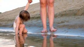 Chłopiec sztuk ręka w wodzie wzdłuż plaży bryzga wodę wokoło i chodzi z jego matką, nogi swobodny ruch zdjęcie wideo