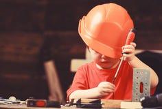 Chłopiec sztuka jako budowniczy lub naprawiacz, praca z narzędziami Dzieciństwa pojęcie Żartuje chłopiec w pomarańczowym ciężkim  obraz stock