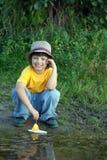 Chłopiec sztuka z jesień liścia statkiem w wodzie, dzieci w parkowych sztuk wi fotografia stock