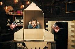 Chłopiec sztuka z rakietą, kosmonauta siedzi w usa podskakuje robi z kartonu Dzieciak excited siedzi w kartonowy ręcznie robiony obrazy stock
