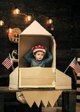Chłopiec sztuka z rakietą, kosmonauta siedzi w usa podskakuje robi z kartonu Dzieciak w hełmie siedzi w kartonowy ręcznie robiony obrazy stock
