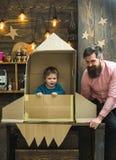 Chłopiec sztuka z tata, ojciec, mały kosmonauta siedzi w rakiecie robić z kartonu Dziecko chłopiec sztuki śliczny kosmonauta zdjęcie stock
