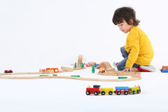 Chłopiec sztuka z zabawka pociągami i dużą drewnianą koleją Obrazy Royalty Free