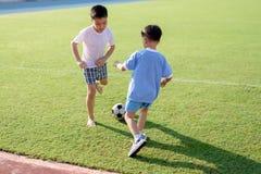 Chłopiec sztuki futbol na gazonie zdjęcia royalty free