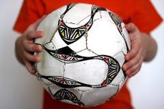 Chłopiec trzyma futbolową piłkę w jego rękach fotografia royalty free