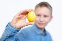 Chłopiec trzyma kolorowych jajka Żółty jajko w chłopiec rękach Rozochocona chłopiec trzyma jajka blisko oczu Biały tło zdjęcia royalty free