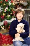Chłopiec trzyma małego szczeniaka psa ono uśmiecha się przed choinką Obrazy Stock