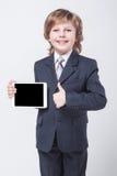 Chłopiec trzyma pastylkę w krawacie i garniturze Zdjęcia Royalty Free