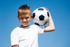 Chłopiec trzyma piłkę zdjęcia stock