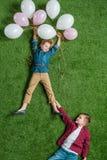 Chłopiec trzyma uśmiechniętej dziewczyny z balonami na trawie Zdjęcia Stock