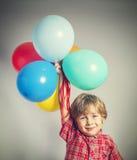 Chłopiec trzyma wiązkę balony fotografia royalty free