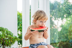 Chłopiec uśmiecha się arbuza i je Fotografia Stock