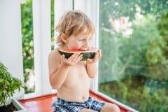 Chłopiec uśmiecha się arbuza i je Zdjęcia Stock