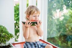 Chłopiec uśmiecha się arbuza i je Obraz Stock
