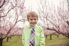 Chłopiec uśmiechnięta pozycja w kwiatonośnych drzewach Fotografia Royalty Free