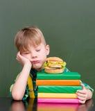Chłopiec uśpiona na stosie książki blisko opróżnia chalkboard Obrazy Royalty Free