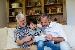 Chłopiec używa cyfrową pastylkę z jego dziadem i ojcem w żywym pokoju Zdjęcia Stock