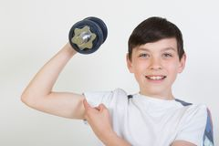 Chłopiec używa dumbbell ciężary Fotografia Royalty Free