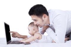Chłopiec używa laptop z jego tata Zdjęcie Royalty Free