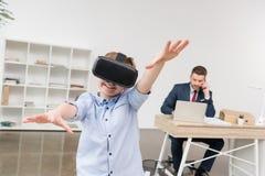Chłopiec używa rzeczywistość wirtualna szkła podczas gdy jego ojca biznesmen fotografia stock