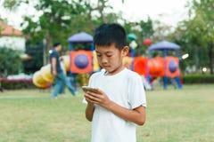 Chłopiec używa smartphone Zdjęcia Stock