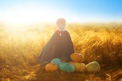 Chłopiec ubierał jako Dracula z baniami dla Halloween nad zmierzchu lub wschodu słońca tłem obraz stock
