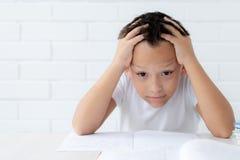 Chłopiec uczeń pisze w notatniku i czytelniczych książkach uczy lekcje fotografia royalty free