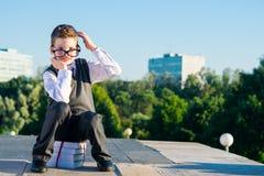 Chłopiec uczeń siedzi na stosie podręczniki, myśleć jego głowę i wziąć up, fotografia stock