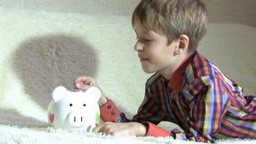 Chłopiec uczeń stawia pieniądze w prosiątko banku zbiory wideo