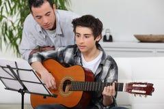 Chłopiec uczy się bawić się gitarę Zdjęcia Royalty Free