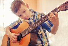 Chłopiec uczy się bawić się gitarę akustyczną W błękitnej koszula Fotografia Royalty Free