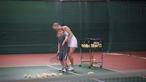 Chłopiec uczy się bawić się tenisa faceta i jego nauczyciela rodzaju, out podstawy tenis w zamkniętym sądzie zbiory