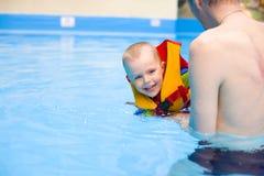 Chłopiec uczy się pływać w basenie z ojcem Zdjęcie Royalty Free