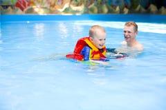 Chłopiec uczy się pływać w basenie z ojcem Obraz Royalty Free