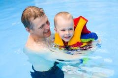 Chłopiec uczy się pływać w basenie z ojcem Fotografia Stock