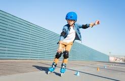 Chłopiec uczy się rolkowa łyżwa na drodze z rożkami obraz royalty free