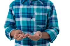 Chłopiec udaje trzymać niewidzialnego przedmiot przeciw białemu tłu Obraz Royalty Free