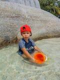 Chłopiec utrzymanie bawi się w morzu szczęśliwie zdjęcie stock