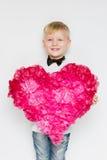 Chłopiec w łęku krawacie dzielił dużego serce od papierowych kwiatów obraz stock