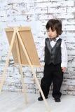 Chłopiec w łęku krawata stojakach obok sztalugi w studiu Obraz Stock