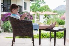 Chłopiec w łozinowym krześle na tarasie Zdjęcie Stock