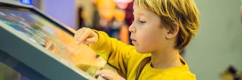 Chłopiec w żółtej kurtce używa ekranu dotykowego sztandar, DŁUGI format obraz royalty free