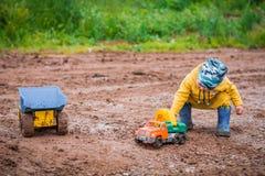 Chłopiec w żółtym kostiumu bawić się z zabawkarskim samochodem w brudzie Fotografia Stock