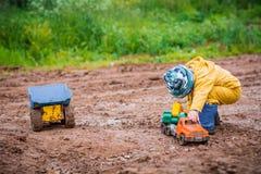 Chłopiec w żółtym kostiumu bawić się z zabawkarskim samochodem w brudzie Obraz Royalty Free