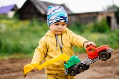 Chłopiec w żółtym kostiumu bawić się z zabawkarskim samochodem w brudzie Obrazy Stock