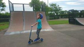 Chłopiec w błękitnej jazdie jego hulajnoga Obrazy Royalty Free