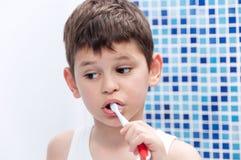 Chłopiec w białej koszulce szczotkuje jego zęby w łazience Obrazy Stock