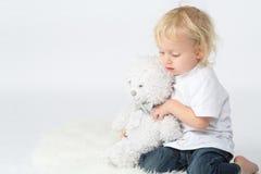 Chłopiec w cajgach z niedźwiedziem w jego wręcza bawić się zdjęcie royalty free