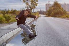 Chłopiec w ciemnej kurtce skacze kałużę na drodze obraz stock