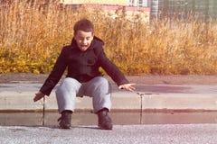 Chłopiec w ciemnej kurtce skacze kałużę na drodze fotografia royalty free